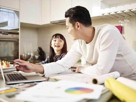 young asian man designer father working at home while taking care of daughter.