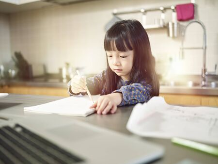 little asian girl sitting at kitchen counter and drawing.