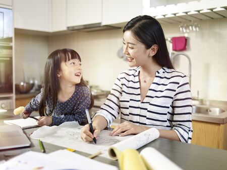 young asian design professional mother working at home while taking care of daughter.