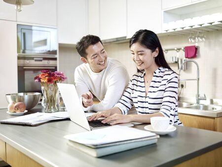 happy young asian couple working together from home talking discussing using laptop computer in kitchen Banco de Imagens