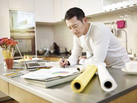 młody azjatycki projektant pracujący w domu, rysujący na papierze kreślarskim