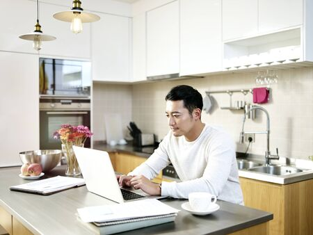 young asian man working from home sitting at kitchen counter using laptop computer Stok Fotoğraf