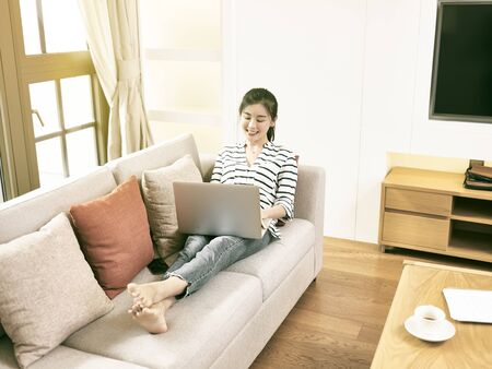 beautiful and happy young asian woman working at home sittng on couch using laptop computer, high angle view