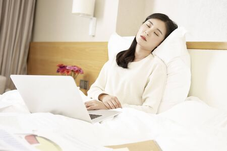 young asian woman falling asleep while working using laptop in bed