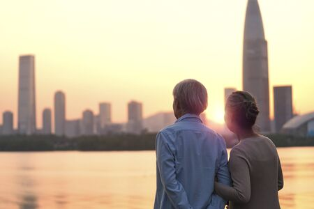 rear view of senior asian couple looking at sunset and city skyline by river