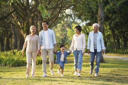 famiglia asiatica felice di tre generazioni che cammina all'aperto nel parco?