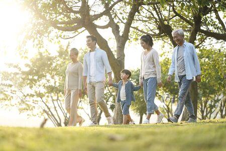 Drei Generationen glückliche asiatische Familie, die draußen im Park spazieren geht Standard-Bild