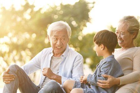 Asiatischer Enkel, Großvater und Großmutter, die in der Abenddämmerung auf Gras im Freien im Park plaudern?