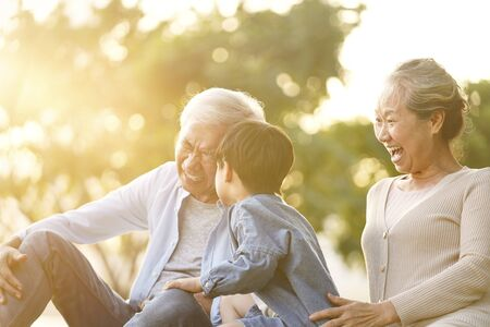 asian grandson, grandfather and grandmother sitting on grass having fun outdoors in park at sunset Stockfoto