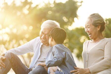 Asiatischer Enkel, Großvater und Großmutter, die auf Gras sitzen und Spaß im Freien im Park bei Sonnenuntergang haben