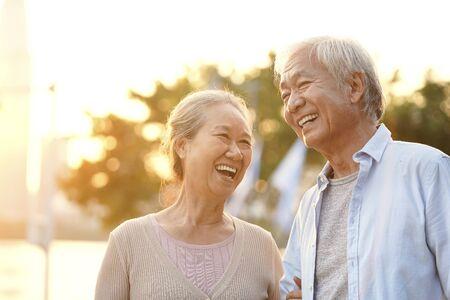 夕暮れ時に公園で屋外で楽しい時間を楽しむシニアアジアのカップル、幸せと笑顔
