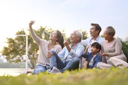 Drei Generationen glückliche asiatische Familie, die auf Gras sitzt und ein Selfie mit dem Handy im Freien im Park macht