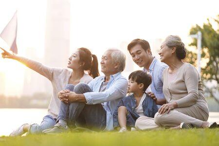 Drei Generationen glückliche asiatische Familie, die auf Gras sitzt und eine gute Zeit in der Abenddämmerung im Freien im Park genießt Standard-Bild