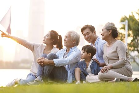 Famille asiatique heureuse de trois générations assis sur l'herbe profitant du bon temps au crépuscule à l'extérieur dans le parc Banque d'images