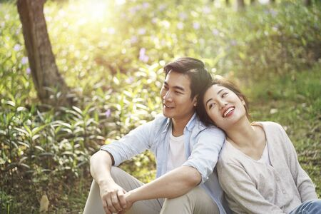 beautiful happy young asian couple sitting on grass talking chatting relaxing in park, high angle view