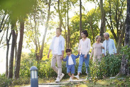 glückliche asiatische Familie mit drei Generationen mit Mutter, Vater, Sohn, Großmutter, Großvater, der sich im Park im Freien entspannt