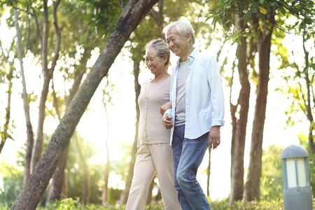 happy senior asian couple walking talking relaxing outdoors in park Standard-Bild