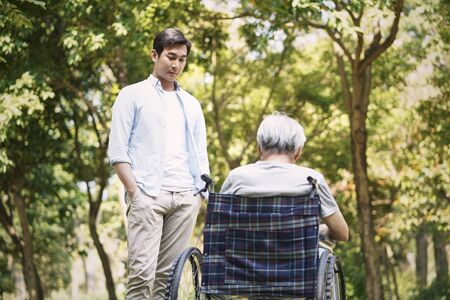 asian son talking to sad and depressed wheelchair bound father