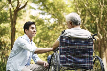 asian son talking to and comforting wheelchair bound father 免版税图像