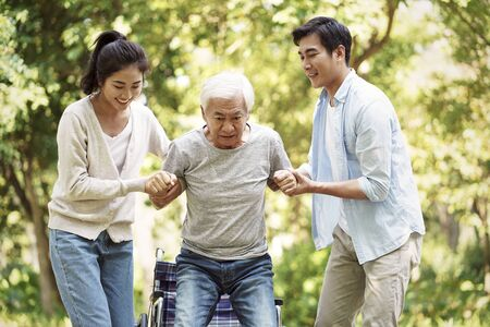 young asian man and woman helping wheelchair bound senior man stand up and walk