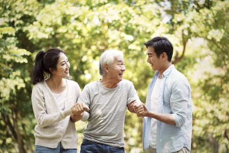 young asian man and woman helping senior man stand up and walk