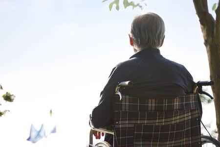 Rückansicht eines asiatischen Senioren, der im Rollstuhl sitzt und in den Himmel schaut
