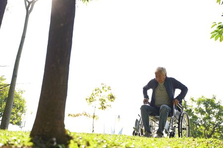 senior asian man trying to get up from wheelchair outdoors