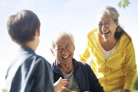 asiatischer Großvater, Großmutter und Enkel haben Spaß im Freien im Park Standard-Bild