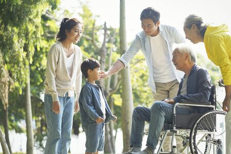 happy asian three generation family having fun outdoors in park