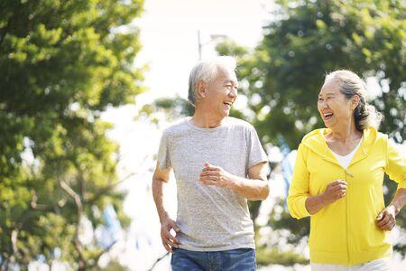 felice vecchia coppia asiatica che fa jogging correndo all'aperto nel parco?