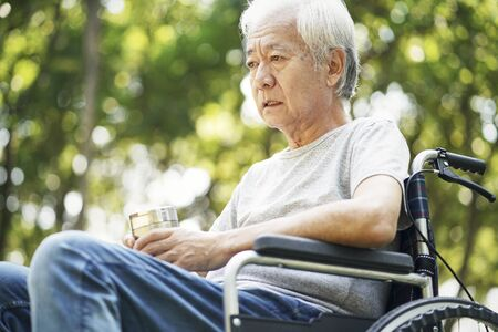 sad asian senior man sitting outdoors in wheelchair 免版税图像