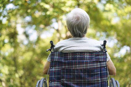 Rückansicht eines asiatischen Senioren, der draußen im Rollstuhl sitzt und seufzend nach oben schaut