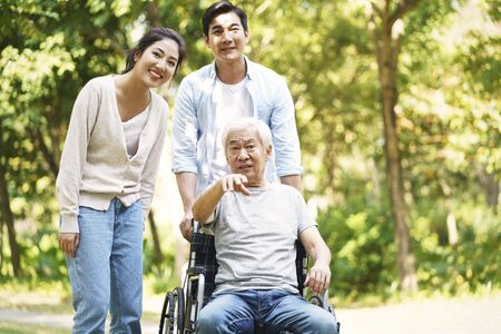 young asian couple and wheelchair bound father relaxing outdoors in park