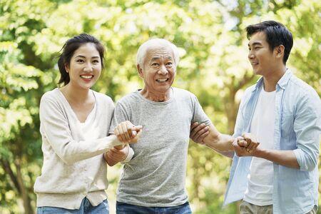 Joven pareja asiática ayudando al padre a ponerse de pie y caminar al aire libre en el parque Foto de archivo