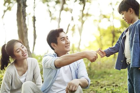 asian father and son sealing a deal by pressing thumbs together outdoors in park Archivio Fotografico