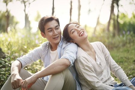 beautiful happy young asian couple sitting on grass talking chatting relaxing in park