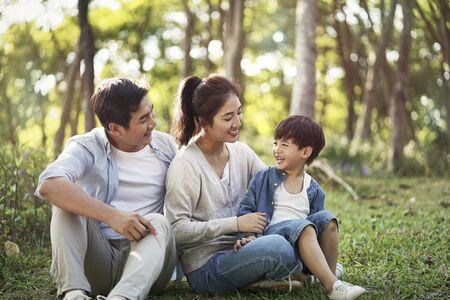 giovani genitori asiatici e figlio che si divertono all'aperto nel parco Archivio Fotografico