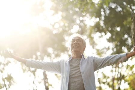 senior asian man enjoying fresh air walking with open arms outdoors in park Foto de archivo - 135461892