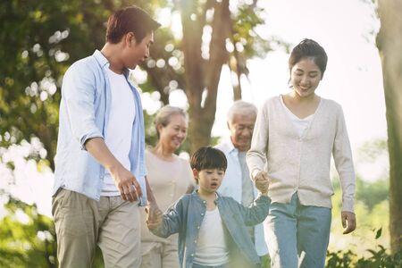 three generation happy asian family walking outdoors in park