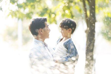 père et fils asiatiques profitant du bon temps à l'extérieur dans le parc