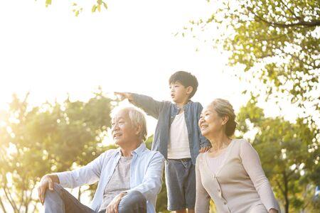 Nieto asiático, abuelo y abuela sentados charlando sobre el césped al aire libre en el parque al atardecer