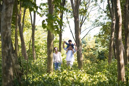 asian parents and child having fun walking outdoors in woods