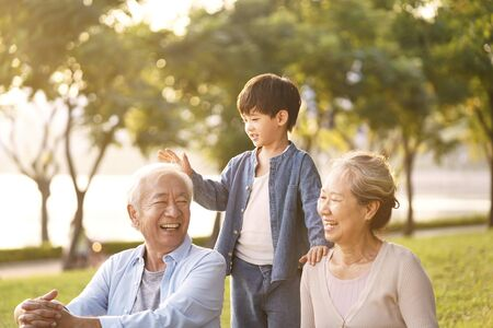 Asian grandparents and grandson chatting while sitting on grass in park outdoors at dusk