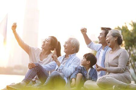 Famille asiatique heureuse de trois générations assise sur l'herbe prenant un selfie à l'aide d'un téléphone portable à l'extérieur dans le parc
