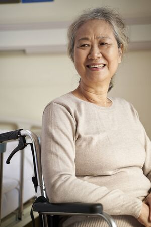 happy senior asian woman sitting in wheel chair in her room in nursing home, happy and smiling