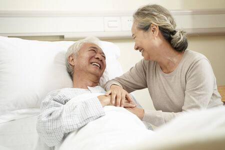 loving and caring senior asian woman visiting and talking to hospitalized husband at bedside