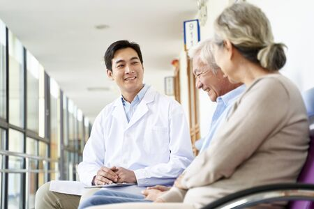 Friendly young asian doctor talking to senior couple in hospital hallway