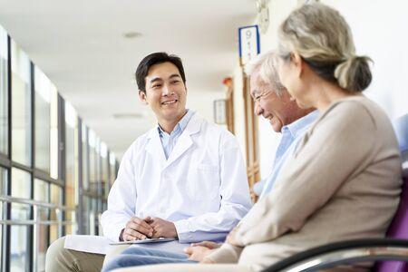 Sympathique jeune médecin asiatique parlant à un couple de personnes âgées dans le couloir de l'hôpital