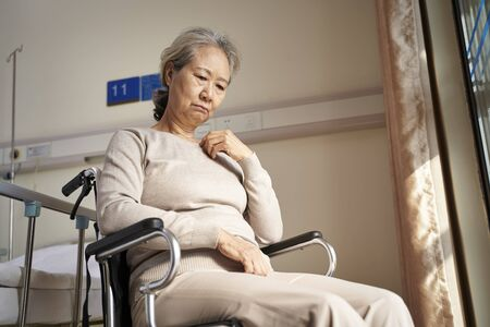 sad and depressed asian elderly woman sitting alone in wheel chair with head down in nursing home Imagens