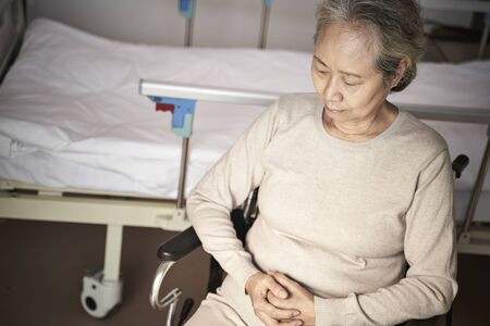 high angle view of sad senior asian woman sitting in wheel chair next to hospital bed